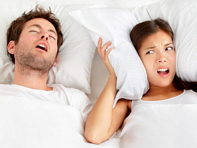man snoring beside a woman covering ears with a pillow