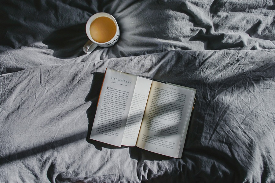 An opened book beside a cup of coffee in the bed